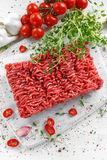 Fresh Raw Beef Minced Meat with salt, pepper, chilli and fresh thyme on white board. Fresh Raw Beef Minced Meat with salt, pepper, chilli and fresh thyme on Royalty Free Stock Photos