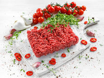 Fresh Raw Beef Minced Meat with salt, pepper, chilli and fresh thyme on white board. Fresh Raw Beef Minced Meat with salt, pepper, chilli and fresh thyme on Stock Image