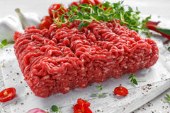 Fresh Raw Beef Minced Meat with salt, pepper, chilli and fresh thyme on white board. Royalty Free Stock Photography