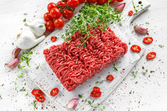 Fresh Raw Beef Minced Meat with salt, pepper, chilli and fresh thyme on white board. Fresh Raw Beef Minced Meat with salt, pepper, chilli and fresh thyme on Stock Photography