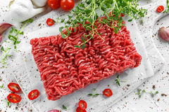 Fresh Raw Beef Minced Meat with salt, pepper, chilli and fresh thyme on white board. Fresh Raw Beef Minced Meat with salt, pepper, chilli and fresh thyme on Stock Photos
