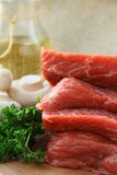 Fresh raw beef  with mushrooms and parsley. On wooden cutting board Stock Photo