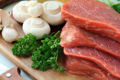 Fresh raw beef  with mushrooms and parsley. On wooden cutting board Royalty Free Stock Photography