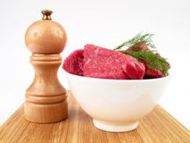 Fresh raw beef and pepper mill. (isolated on white background Royalty Free Stock Photo