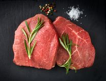 Raw beef steaks with rosemary. Fresh raw beef with rosemary on black background Royalty Free Stock Photos