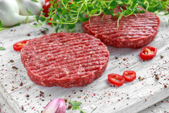 Fresh raw beef, round patties for making homemade burger on wooden white board.  Royalty Free Stock Images