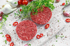 Fresh raw beef, round patties for making homemade burger on wooden white board.  Stock Images