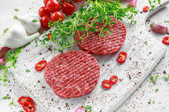 Fresh raw beef, round patties for making homemade burger on wooden white board.  Stock Photography