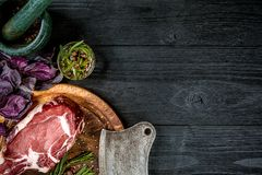 Fresh raw beef with basil and a sprig of rosemary with ax for meat on black wooden background. Top view. Fresh raw beef with spices, fresh basil and a sprig of Royalty Free Stock Photo