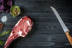 Fresh raw beef with basil and a sprig of rosemary with knife with a wooden handle on black wooden background. Top view Stock Photos
