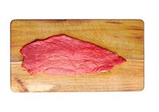 Fresh raw beef steak in black on wooden board. Fresh raw beef steak in black on kitchen wooden board isolated on white background Stock Photography
