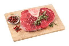 Fresh raw beef steak with bone on cutting board. On white background Royalty Free Stock Photo