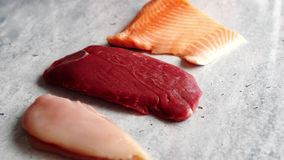Fresh raw beef steak, chicken breast, and salmon fillet stock video
