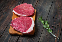 Fresh raw beef steak and chilli pepper on wood.  Royalty Free Stock Photo