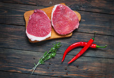 Fresh raw beef steak and chilli pepper on wood.  Stock Photography