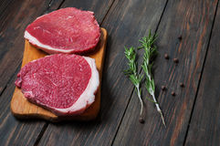 Fresh raw beef steak and chilli pepper on wood.  Royalty Free Stock Image