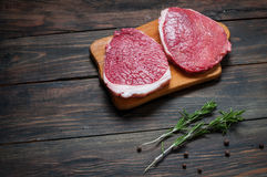 Fresh raw beef steak and chilli pepper on wood.  Royalty Free Stock Photos