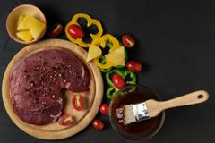 Fresh raw beef steak with barbecue sauce. Fresh raw beef steak with dry rosemary leaf and pepper with barbecue sauce on black table background, Marinated meat Stock Photography