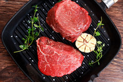 Fresh Raw Beef steak Mignon, with salt, peppercorns, thyme, garlic. Stock Image