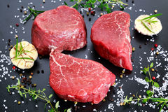 Fresh Raw Beef steak Mignon, with salt, peppercorns, thyme, garlic. Royalty Free Stock Image