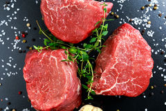 Fresh Raw Beef steak Mignon, with salt, peppercorns, thyme, garlic. Royalty Free Stock Photo