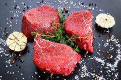 Fresh Raw Beef steak Mignon, with salt, peppercorns, thyme, garlic. Stock Images