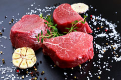 Fresh Raw Beef steak Mignon, with salt, peppercorns, thyme, garlic. Royalty Free Stock Photos
