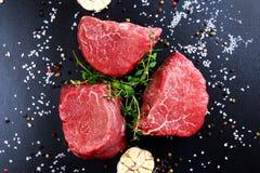 Fresh Raw Beef steak Mignon, with salt, peppercorns, thyme, garlic. Fresh Raw Beef steak Mignon, with salt, peppercorns, thyme, garlic Ready to cook Stock Photo