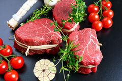 Fresh Raw Beef steak Mignon, with salt, peppercorns, thyme, tomatoes. Ready to cook Royalty Free Stock Photos