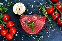 Fresh Raw Beef steak Mignon, with salt, peppercorns, thyme, tomatoes. Ready to cook Royalty Free Stock Image