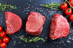 Fresh Raw Beef steak Mignon, with salt, peppercorns, thyme, tomatoes. Ready to cook Stock Photo