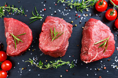 Fresh Raw Beef steak Mignon, with salt, peppercorns, thyme, tomatoes. Ready to cook Royalty Free Stock Photography