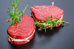 Fresh Raw Beef steak Mignon with thyme. Fresh Raw Beef steak Mignon with thyme on black background Royalty Free Stock Image