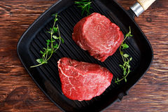Fresh Raw Beef steak Mignon with thyme on grilled pan Royalty Free Stock Photography
