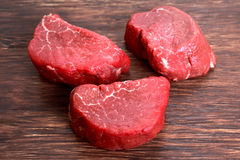 Fresh Raw Beef steak Mignon on wooden board. Ready to cook Royalty Free Stock Photo