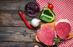Fresh raw beef steak and pepper on wood.  Stock Image