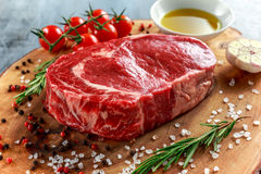 Fresh Raw Beef Steak Ribeye, with salt, peppercorns, rosemary, tomatoes and olive oil.  Royalty Free Stock Image