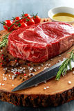 Fresh Raw Beef Steak Ribeye, with salt, peppercorns, rosemary, tomatoes and olive oil.  Stock Photo