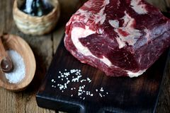 Fresh raw beef steak with sea salt on a serving board on an old wooden background. Food Stock Photo
