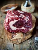 Fresh raw beef steak with sea salt on a serving board on an old wooden background. Stock Photo