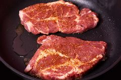 Fresh raw beef steak with spices on frying pan. organic farm.  Royalty Free Stock Image