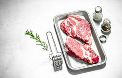 Fresh raw beef steak with spices. On rustic background Royalty Free Stock Images