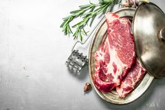 Fresh raw beef steak with spices. On rustic background Stock Photos