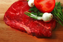 Fresh raw beef steak and vegetables. Fresh raw beef steak on cutting board and vegetables Stock Image