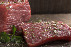 Fresh raw beef steak. On wood with salt and herbs Royalty Free Stock Image