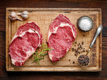 Fresh raw beef steak. On wooden cutting board, top view Royalty Free Stock Image