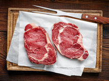 Fresh raw beef steak. On wooden cutting board, top view Stock Photography