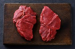 Fresh raw beef steaks on a dark wooden background. Flat lay Royalty Free Stock Image
