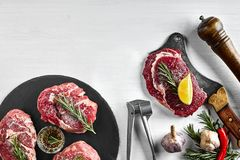 Fresh raw beef steaks with herbs, garlic, olive oil, pepper, salt and rosemary on black board: Tenderloin, Striploin. Rib Eye and a kitchen ax on white Stock Photo