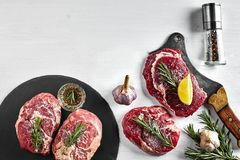Fresh raw beef steaks with herbs, garlic, olive oil, pepper, salt and rosemary on black board: Tenderloin, Striploin. Rib Eye and a kitchen ax on white Royalty Free Stock Photos